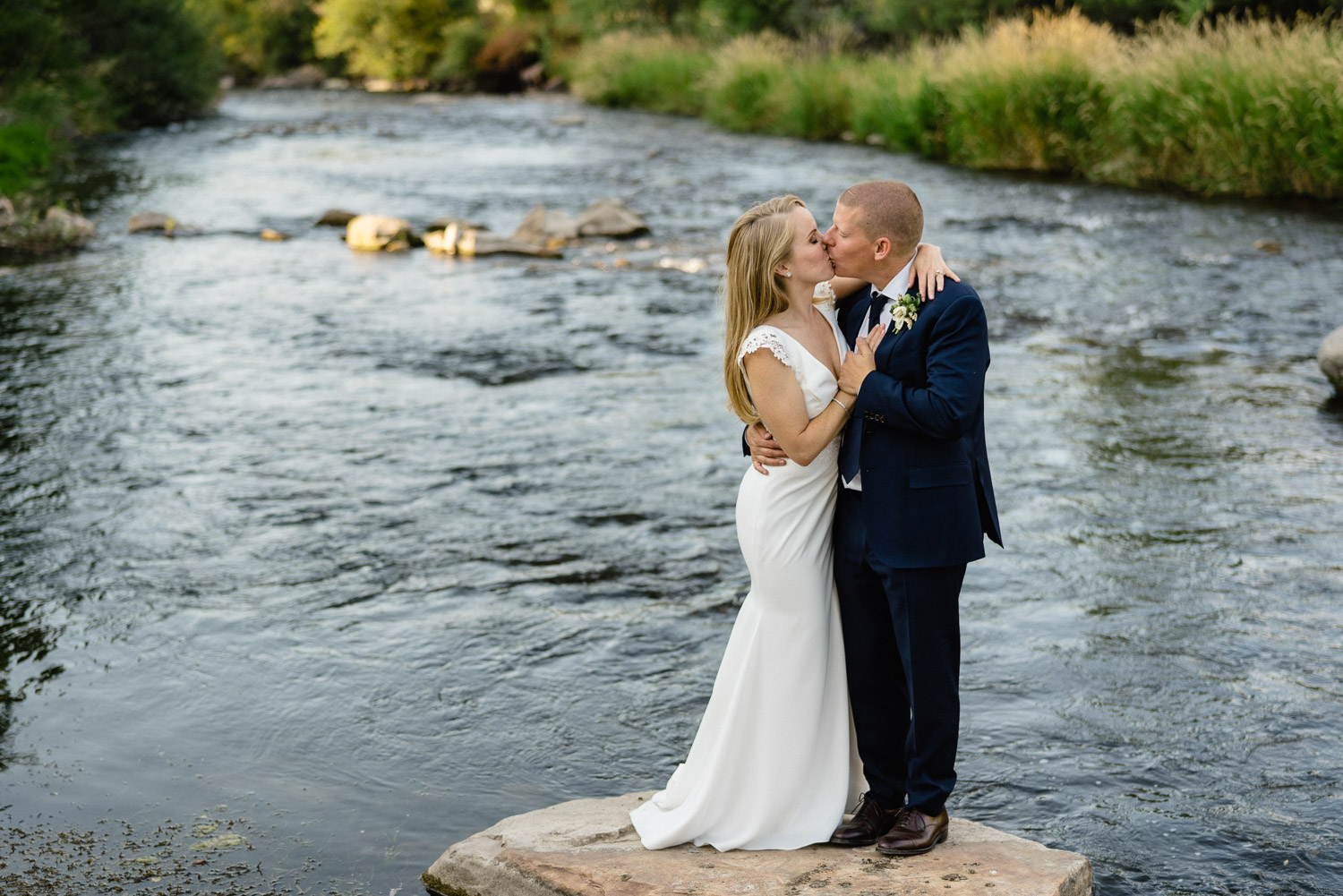 bride and groom kissing standing on a rock in river park city wedding