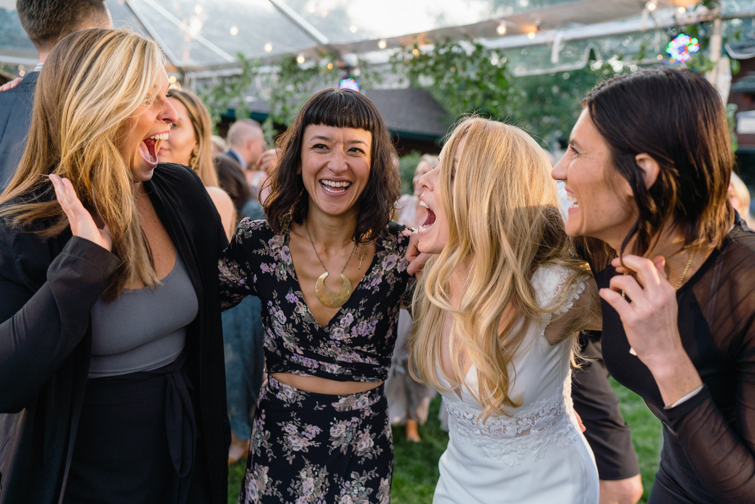 bride with girlfriends laughing in yard outdoor park city wedding