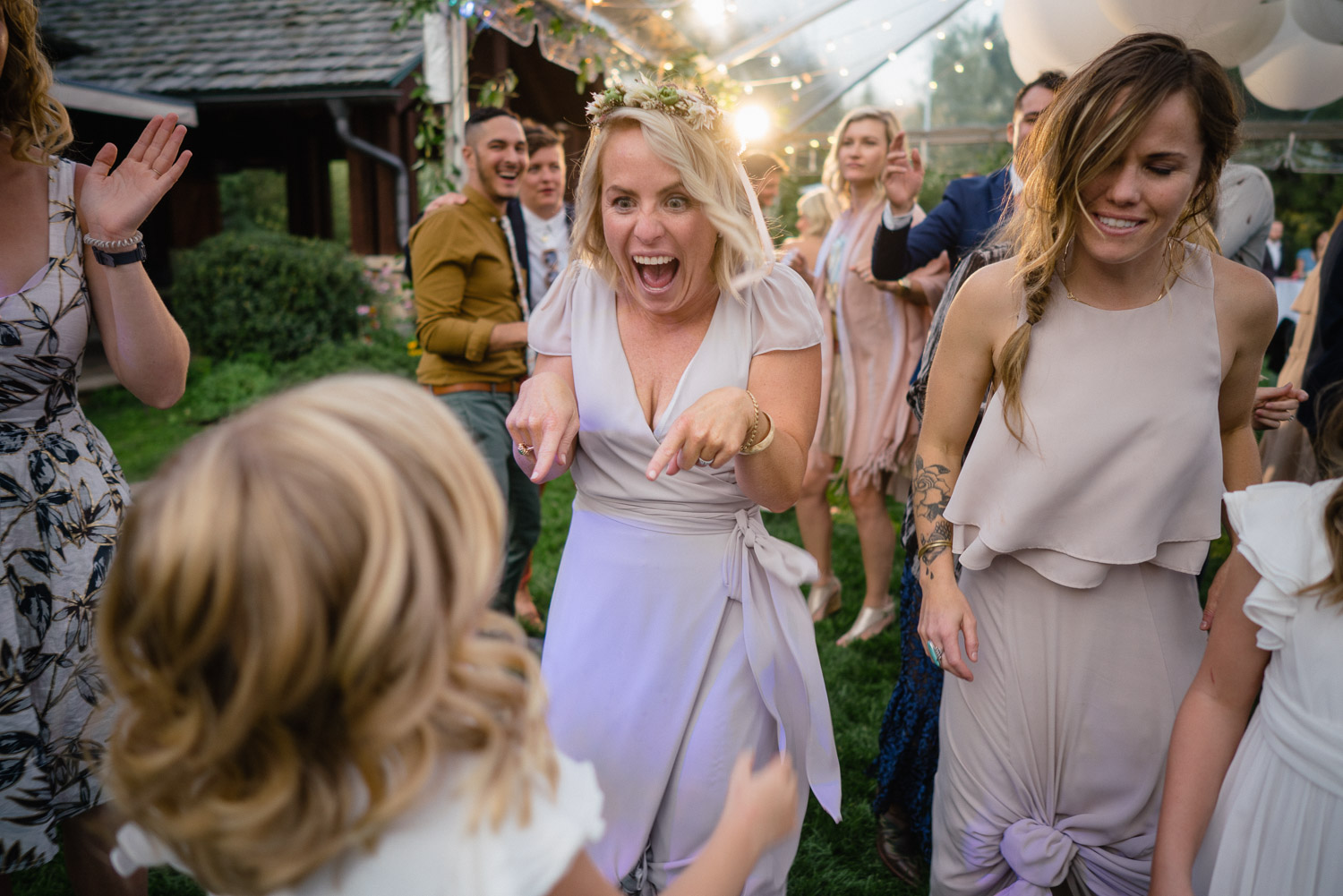 bride and guests dancing under lights outside park city wedding