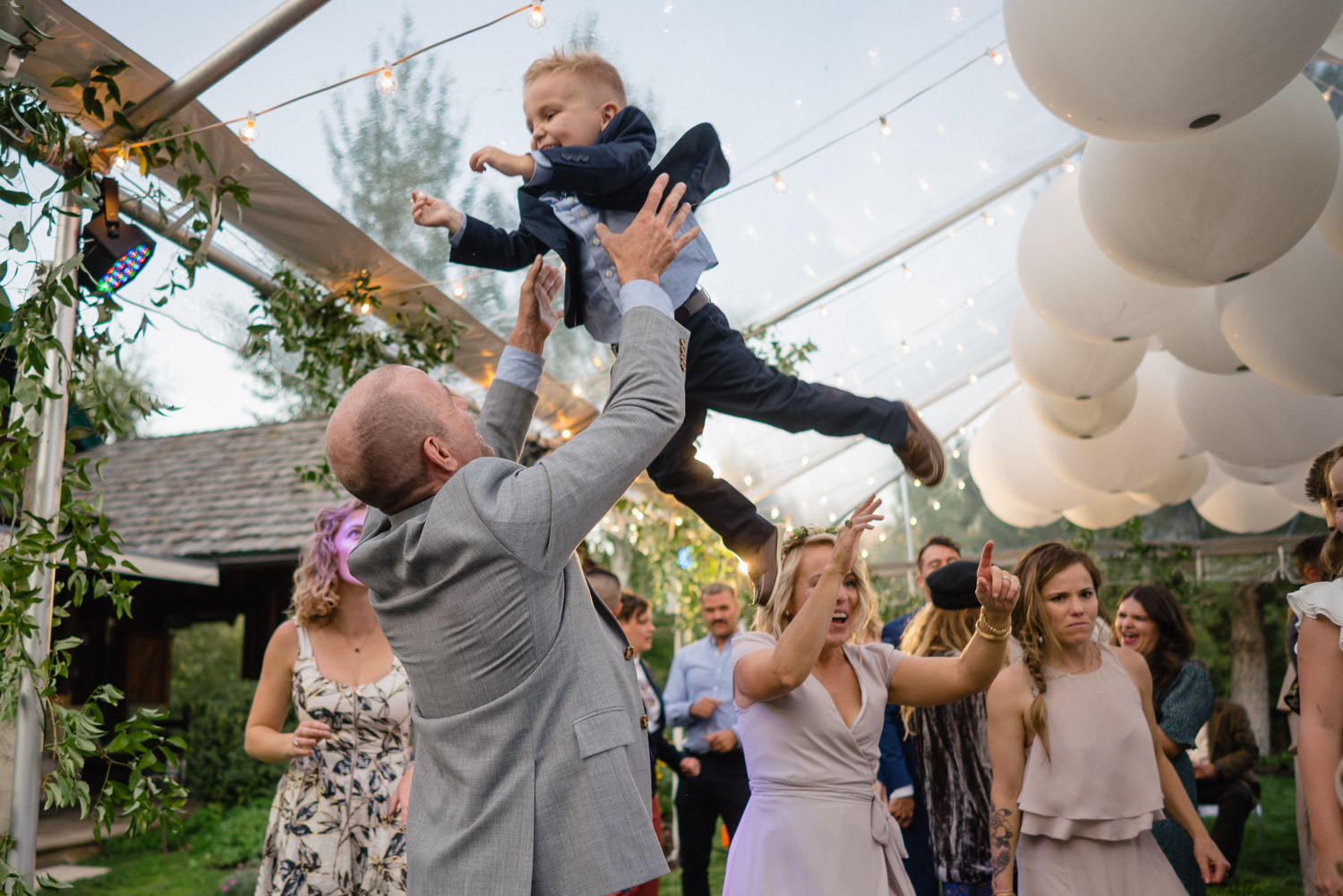 man tossing kid celebration outdoor wedding