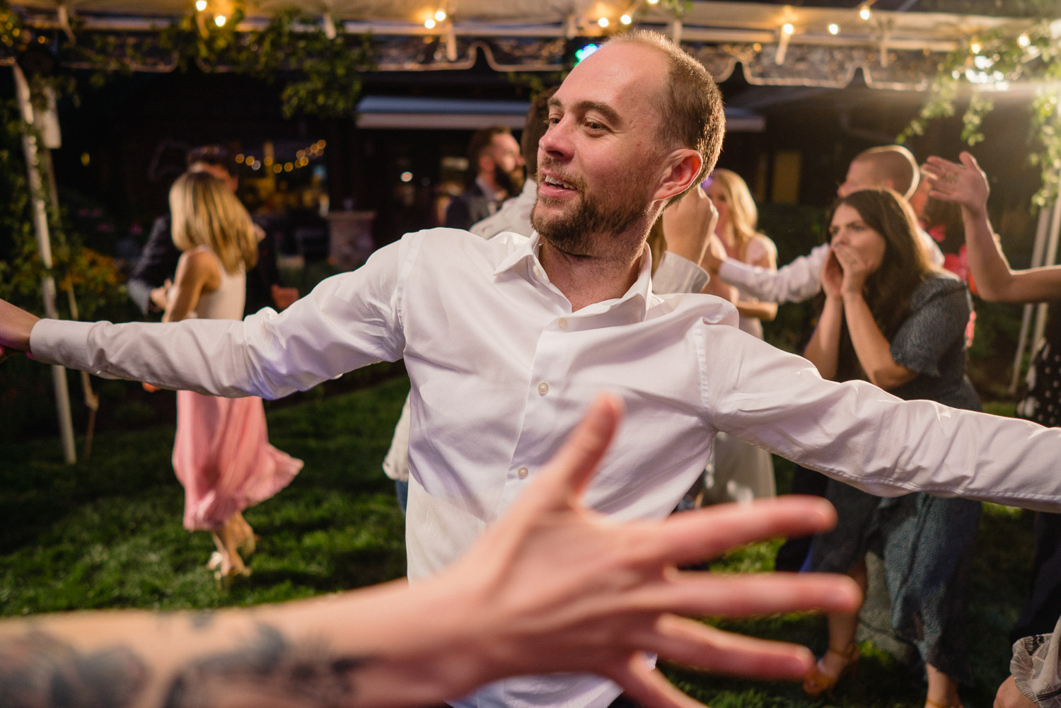 guests dancing under night lights outdoor park city wedding