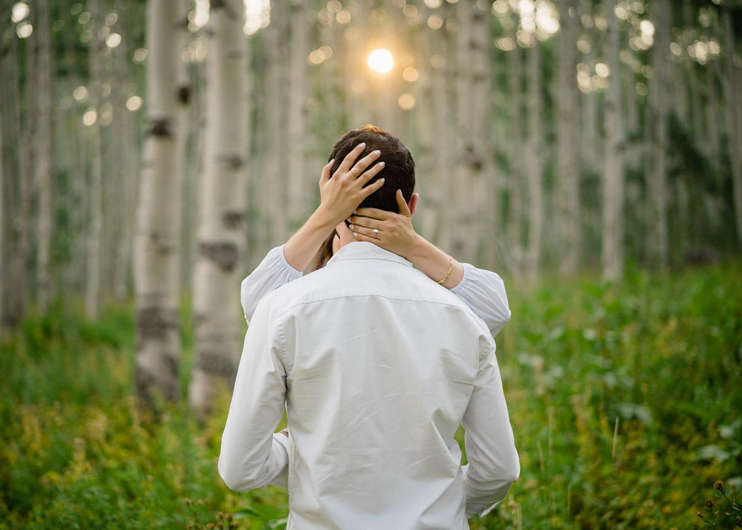 woman hugging man aspen trees engagements