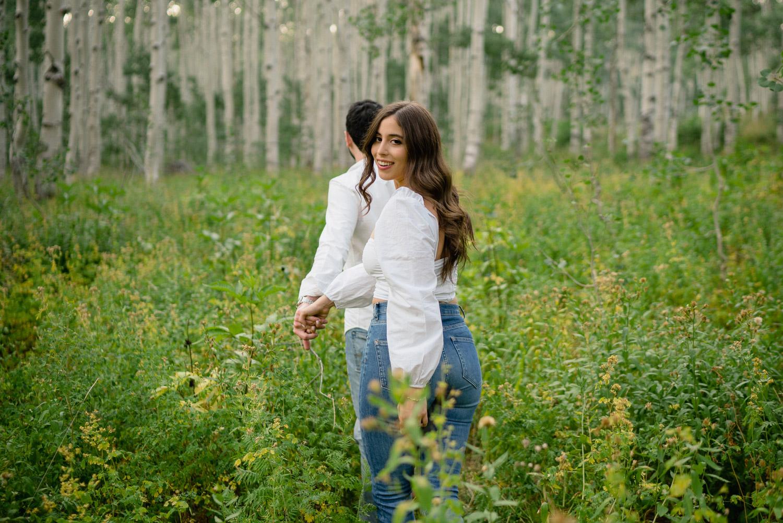 couple walking through wildflowers engagements utah