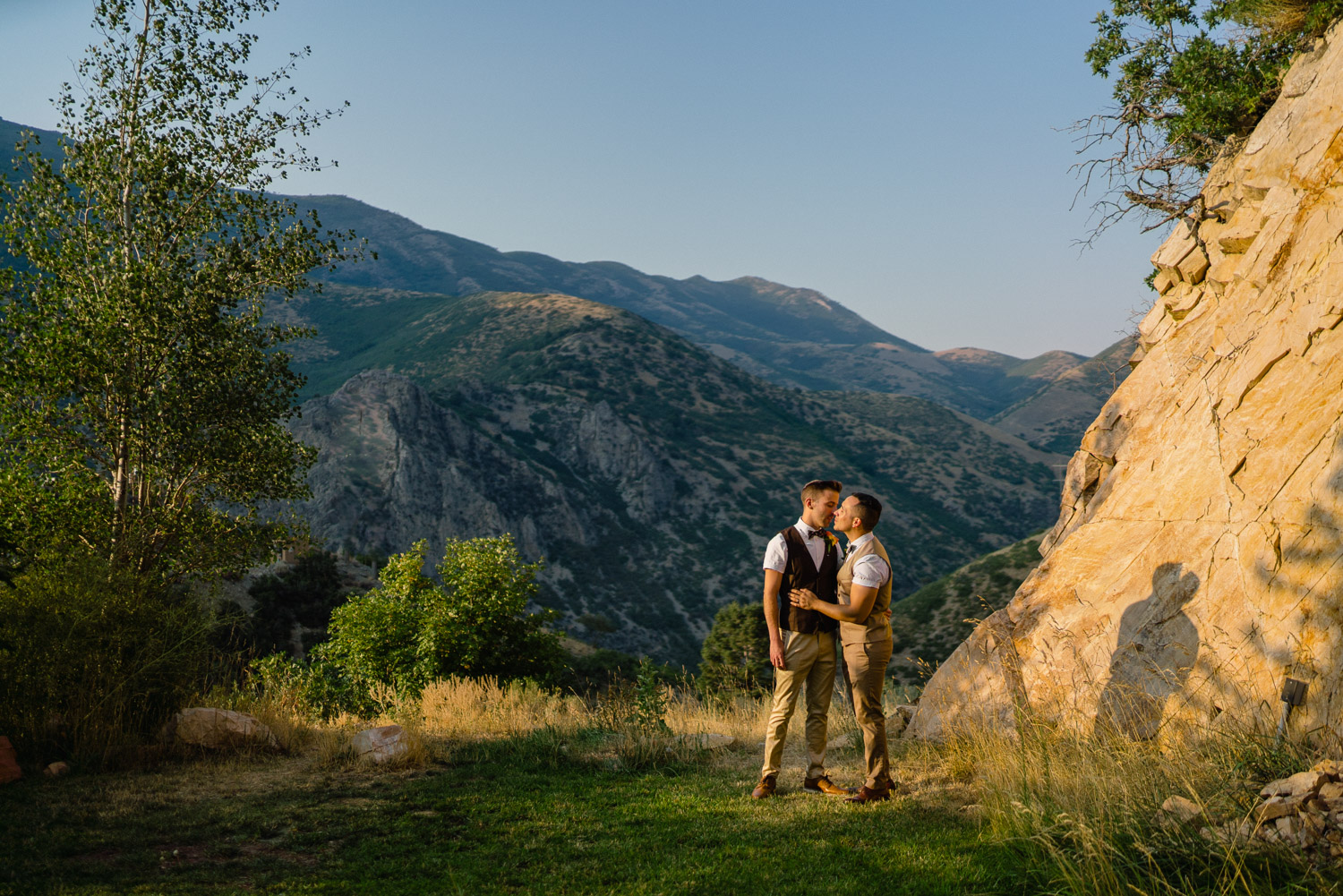 grooms kissing outside with mountains and blue sky louland falls