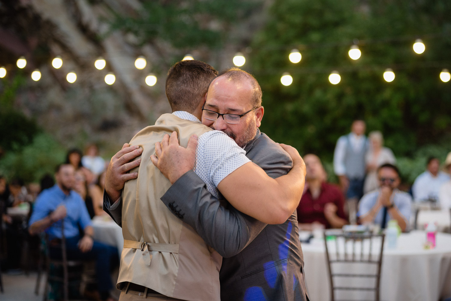 groom hugging man under lights louland falls
