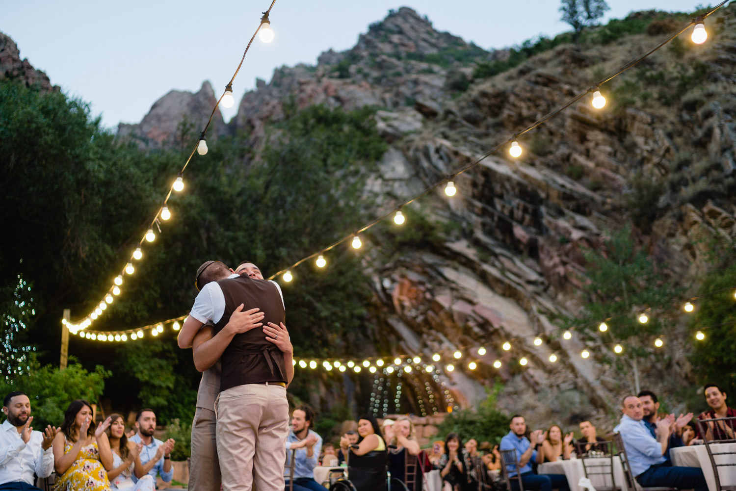 grooms hugging under lights and mountain louland falls wedding