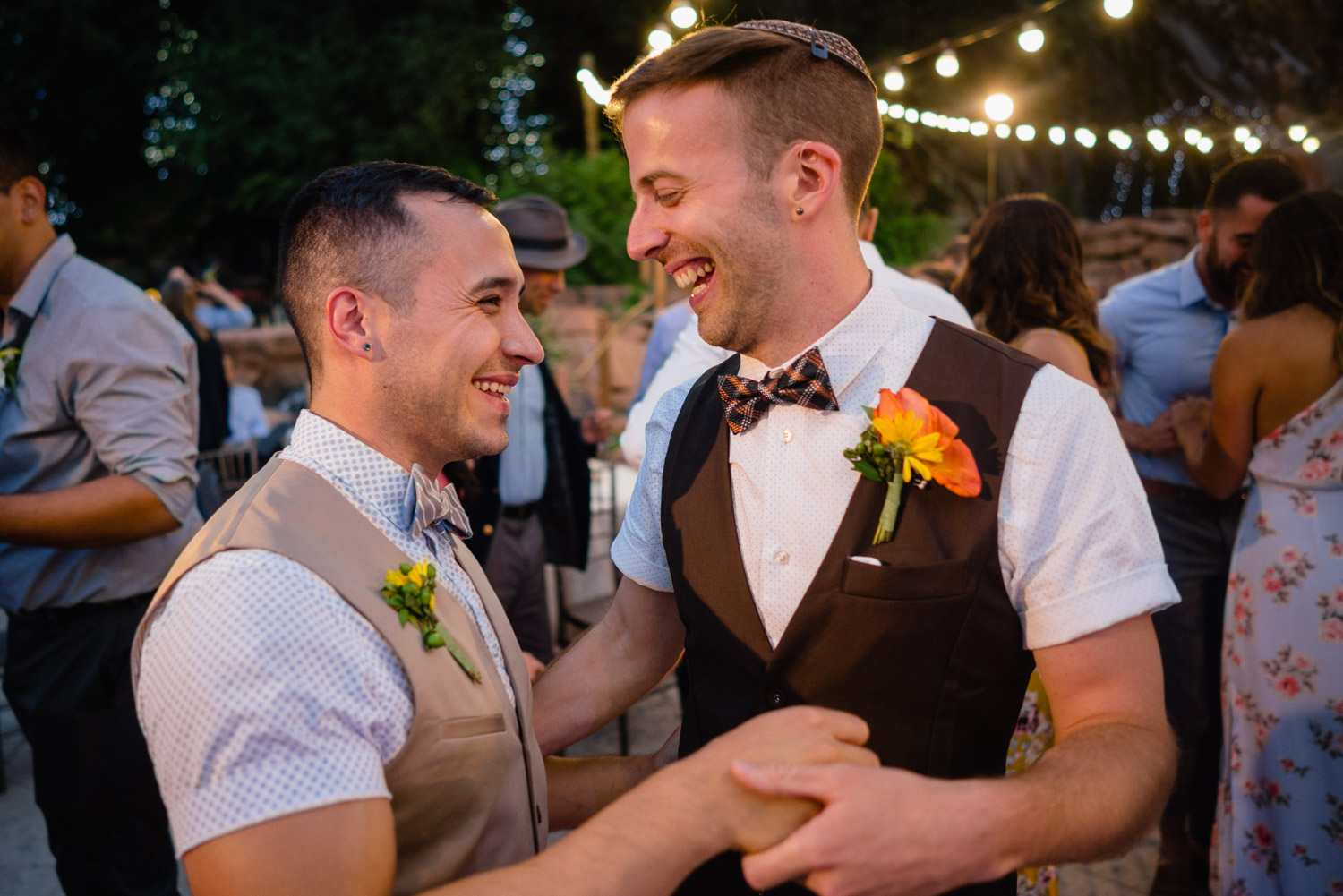 grooms laughing and holding hands at outdoor mountain reception