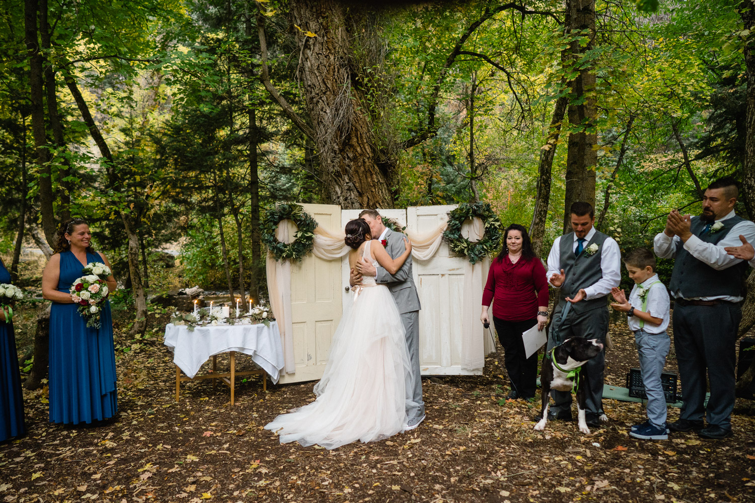 bride and groom kissing at outdoor altar with wedding party millcreek canyon utah