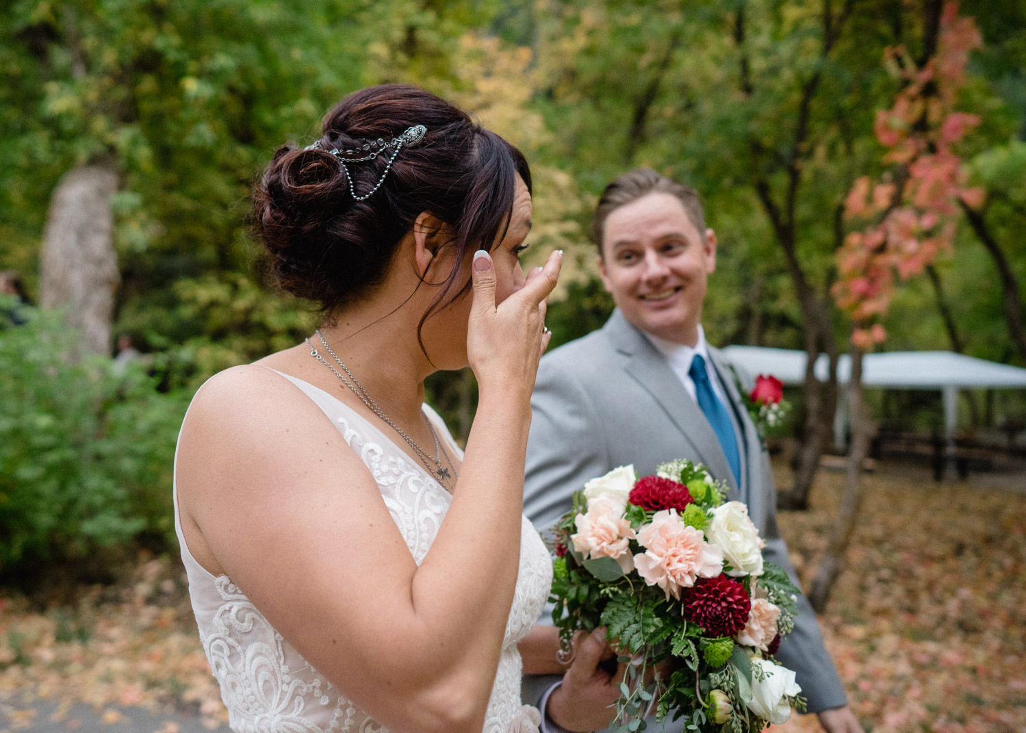 bride wiping tear groom smiling outside fall wedding millcreek canyon