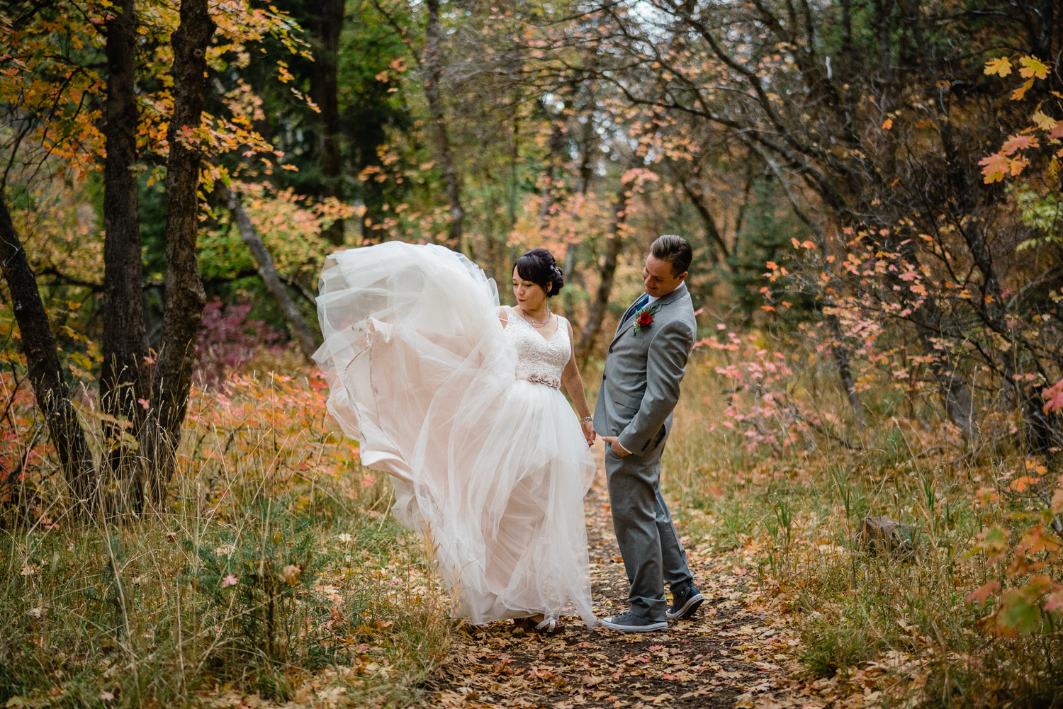 bride and groom on leaf covered path with trees train blowing up millcreek canyon
