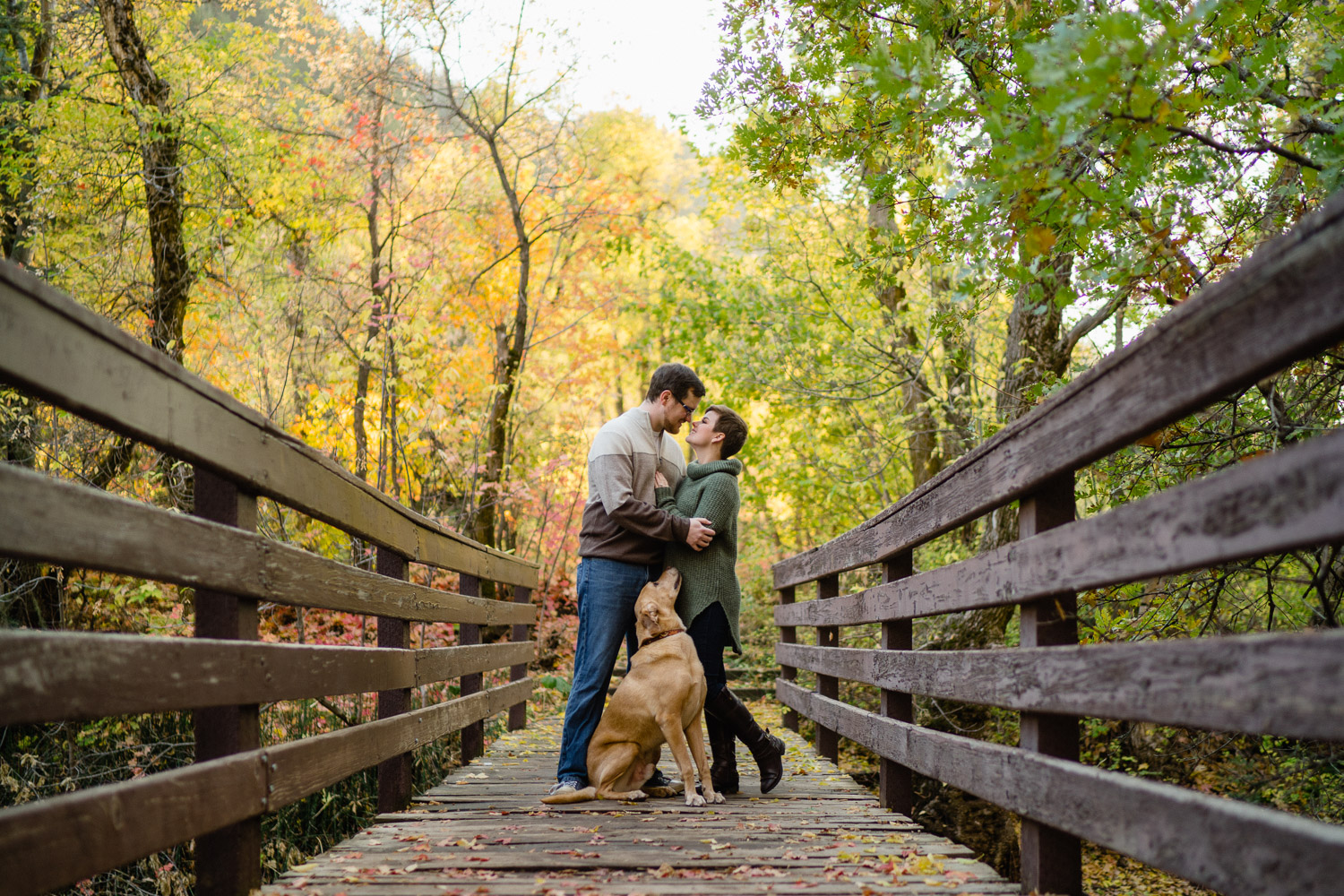 happy couple on bridge looking at each other with dog and trees