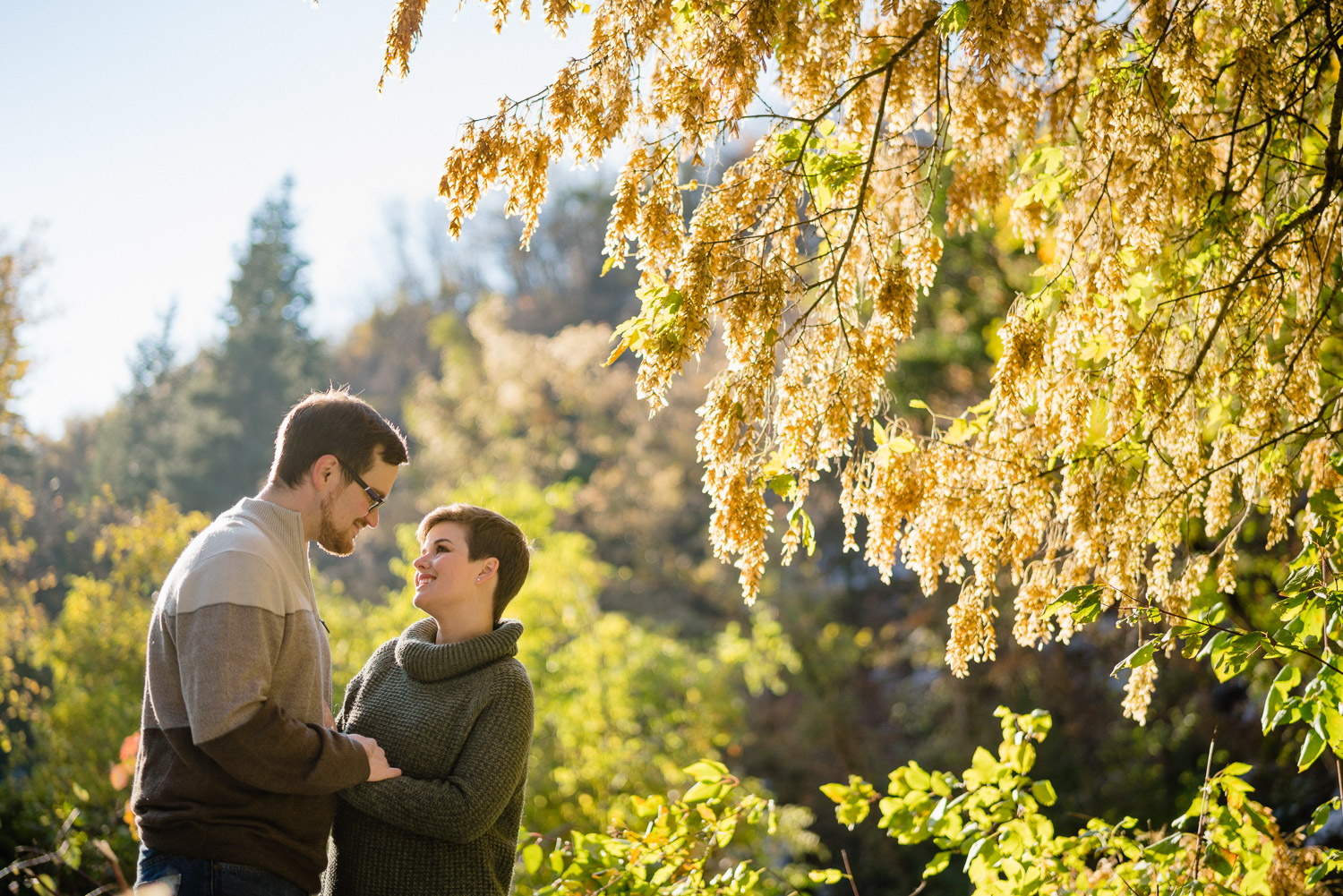 happy couple smiling in trees under blue sky utah engagements