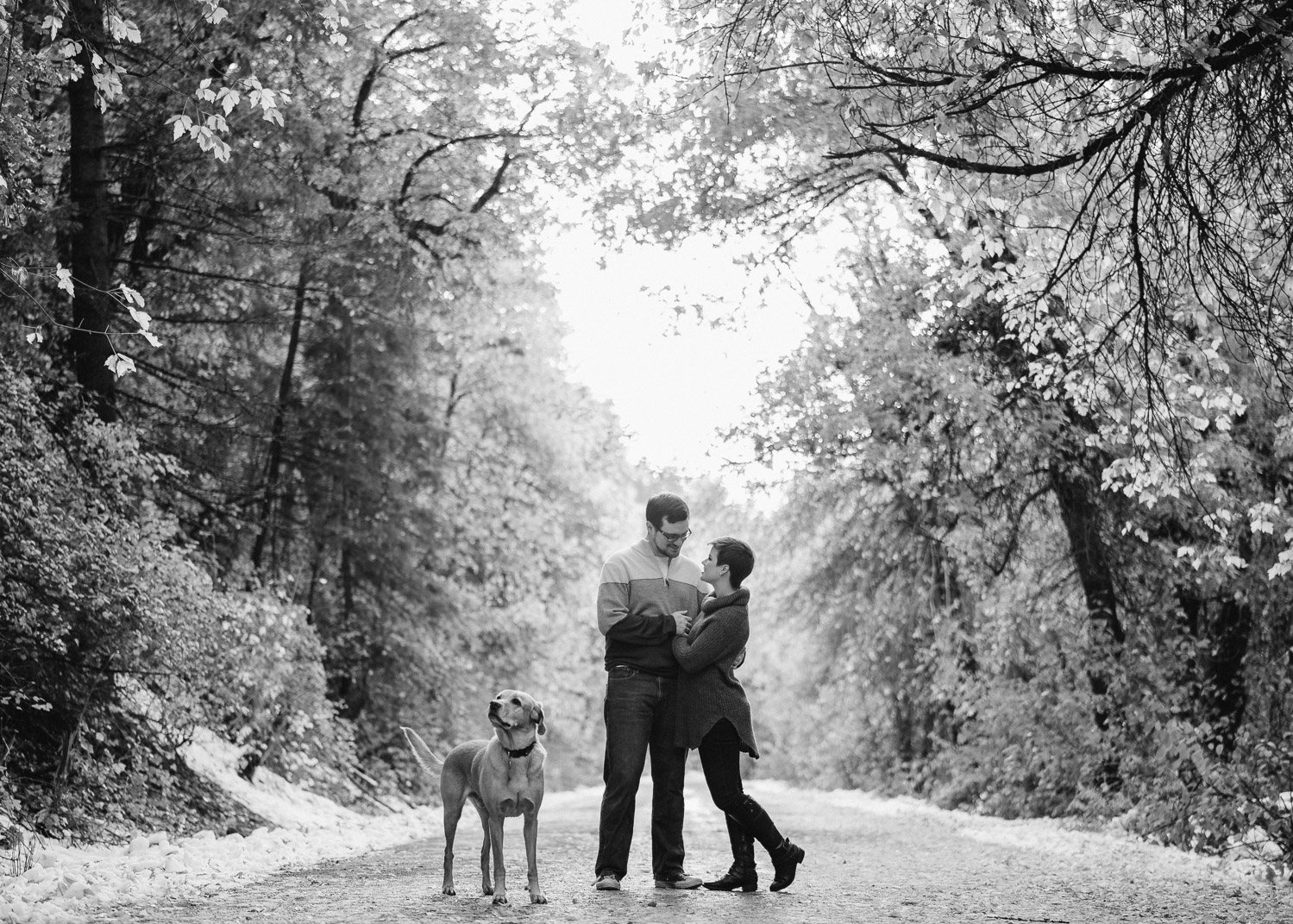 happy couple and dog with trees black and white