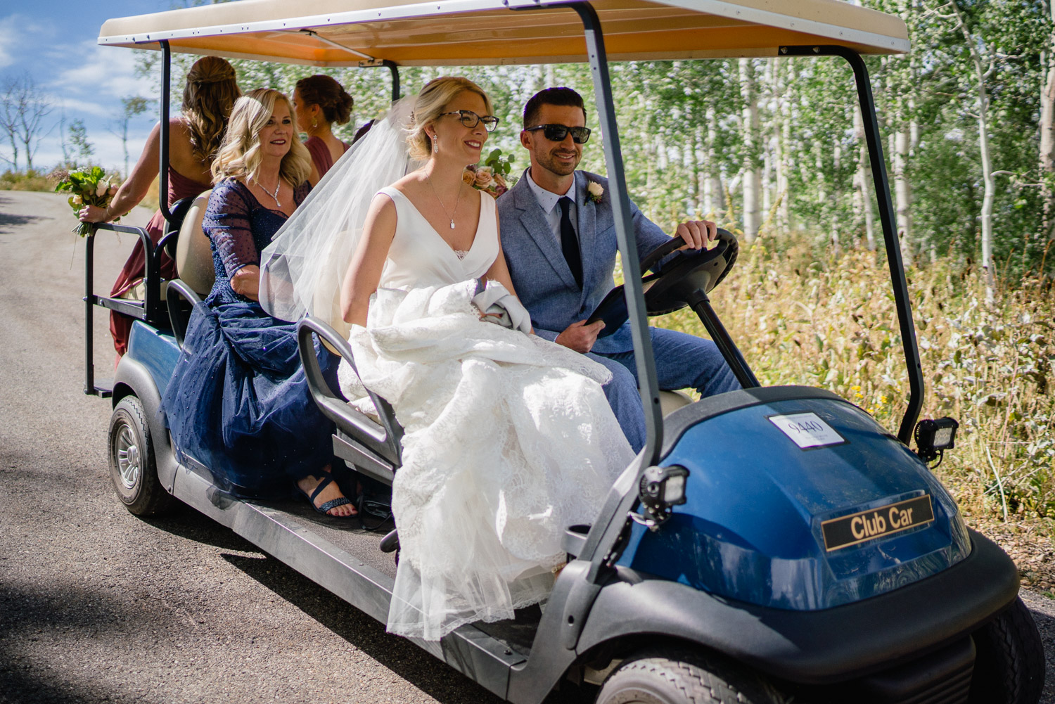 bride and wedding party riding in golf cart park city
