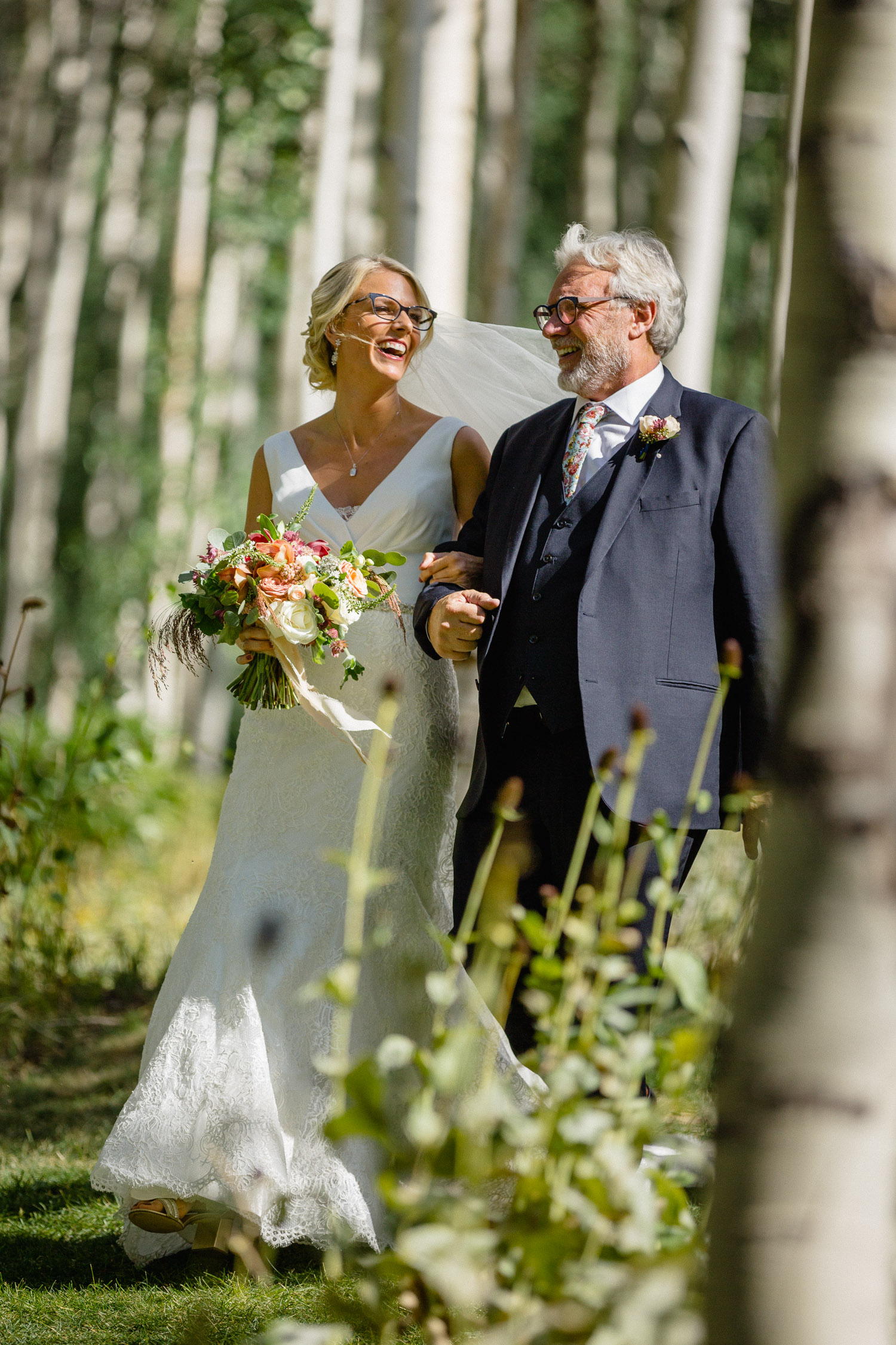 father walking bride down outside aisle in trees
