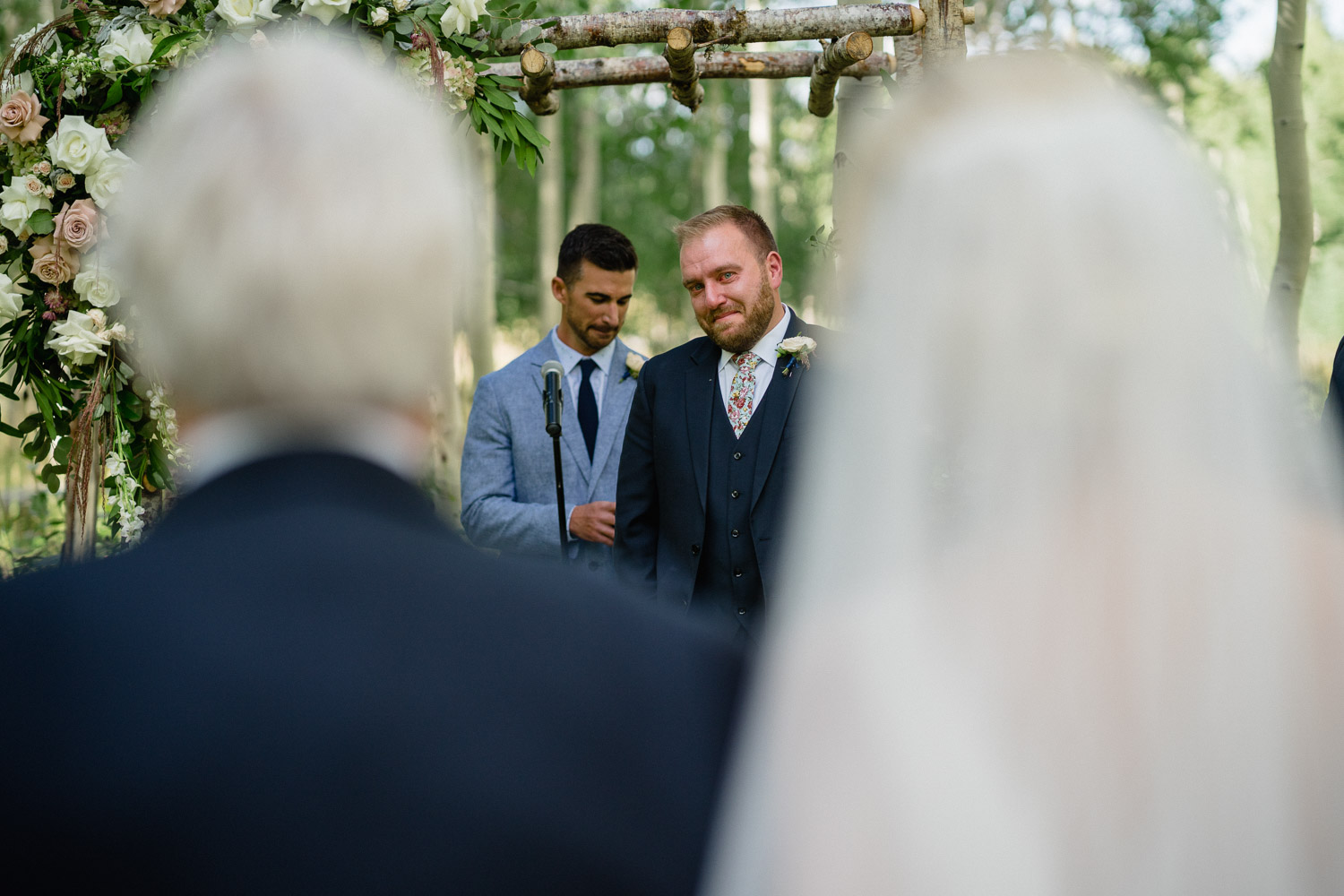 groom smiling at bride walking down aisle outside park city wedding