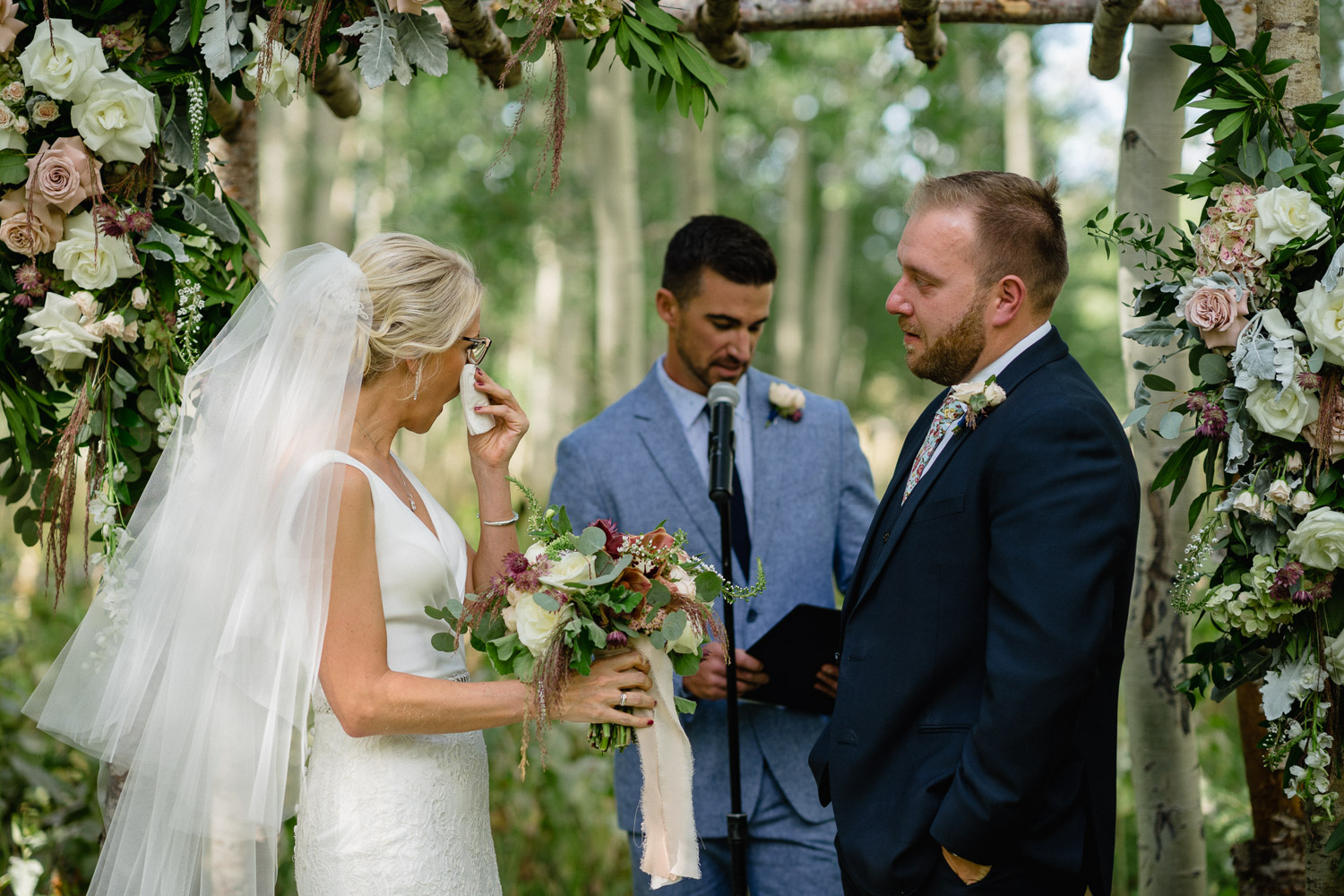 bride wiping tears with groom and officiant under outdoor altar