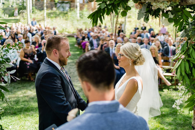 bride and groom facing wedding guests outdoor ceremony