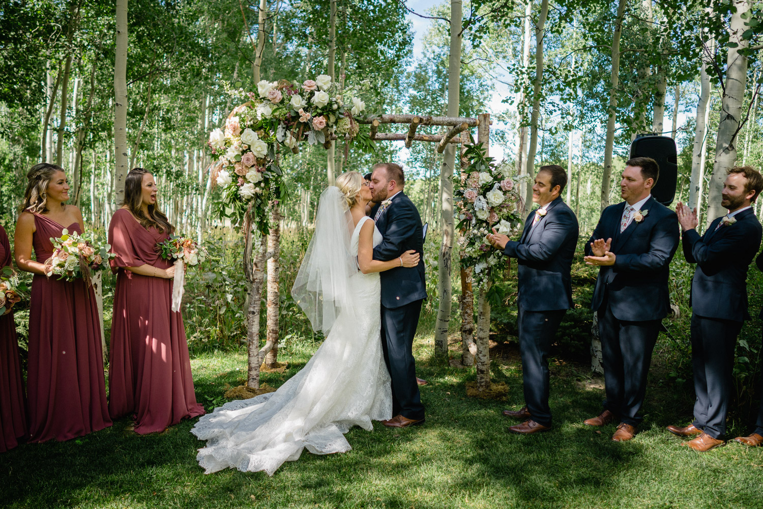 bride and groom first kiss outdoor wedding park city