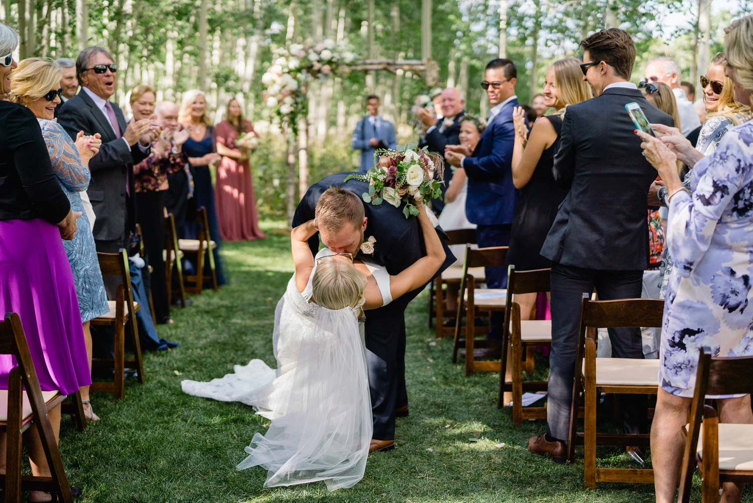 groom dipping and kissing bride down aisle guests cheering park city