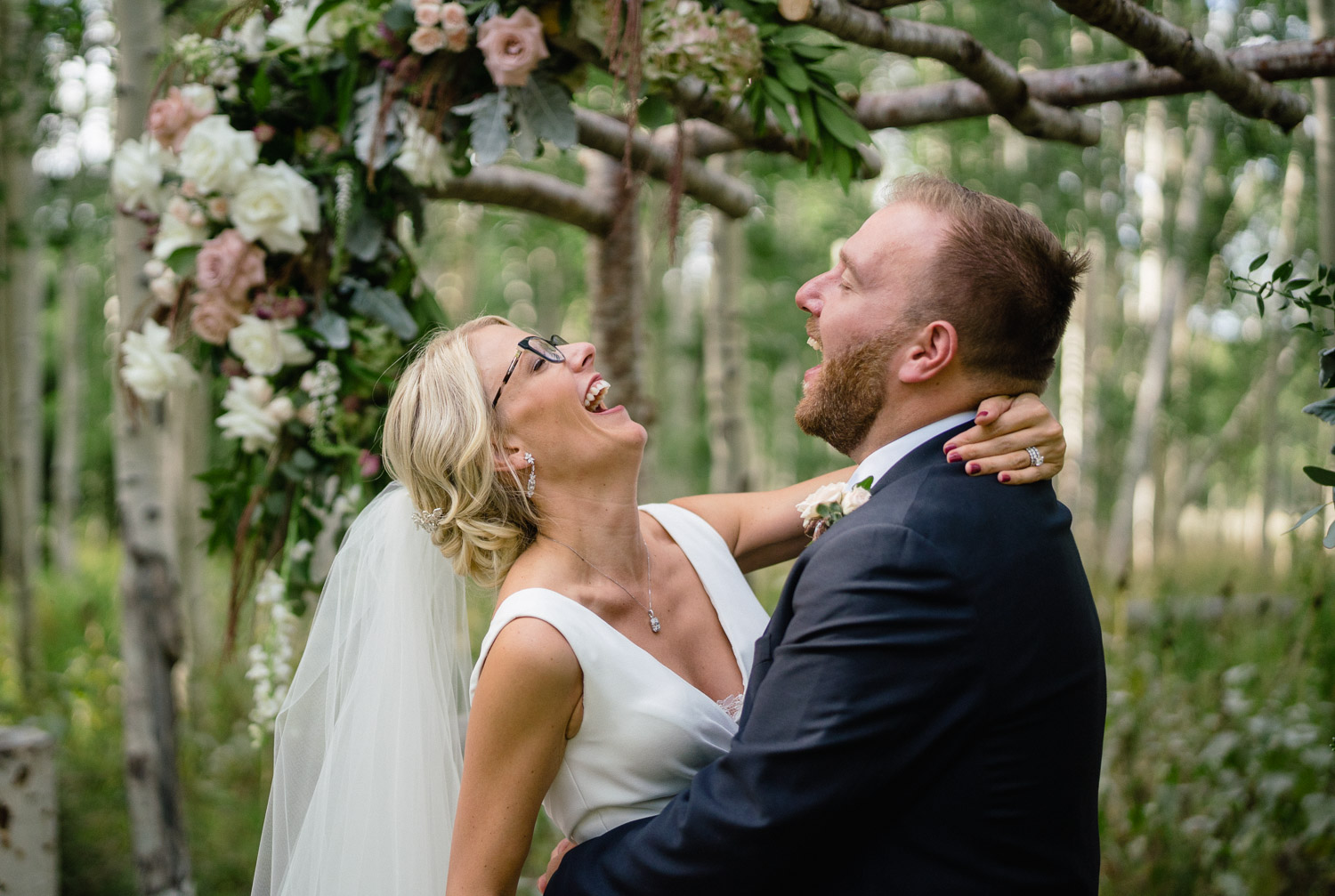bride and groom laughing by outdoor altar
