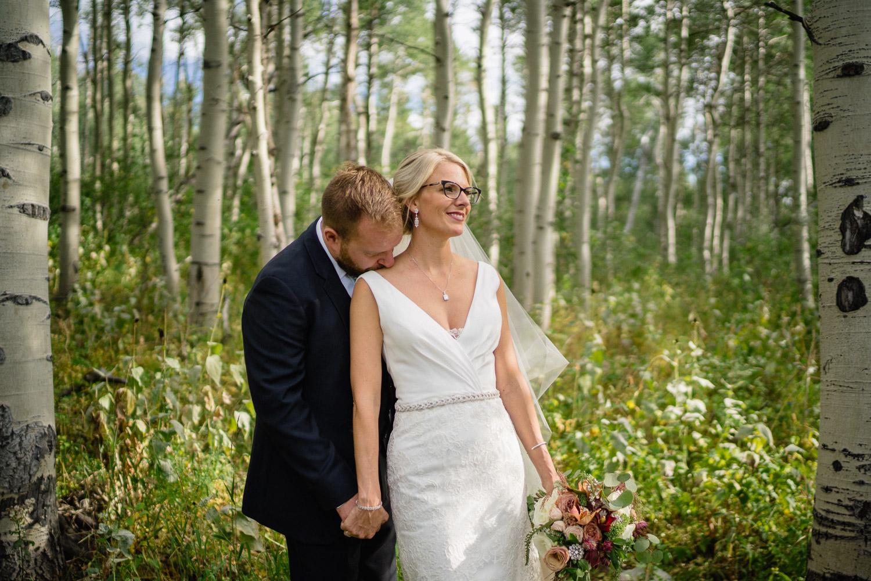 groom kissing brides shoulder bride smiling outside in trees
