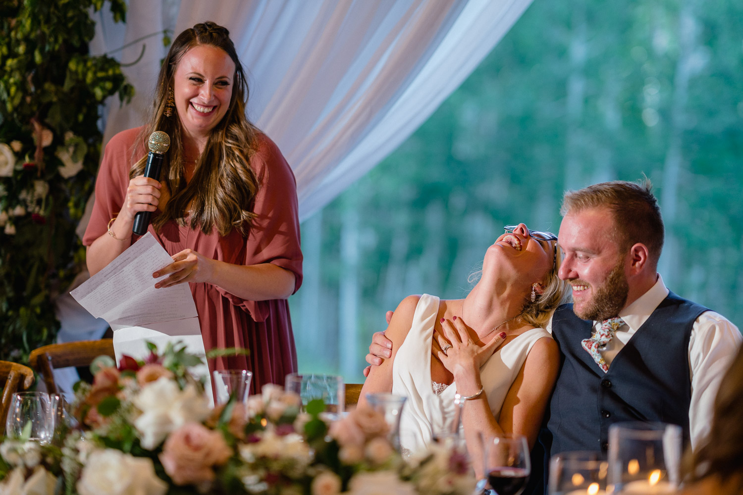 woman giving toast bride laughing groom smiling reception park city