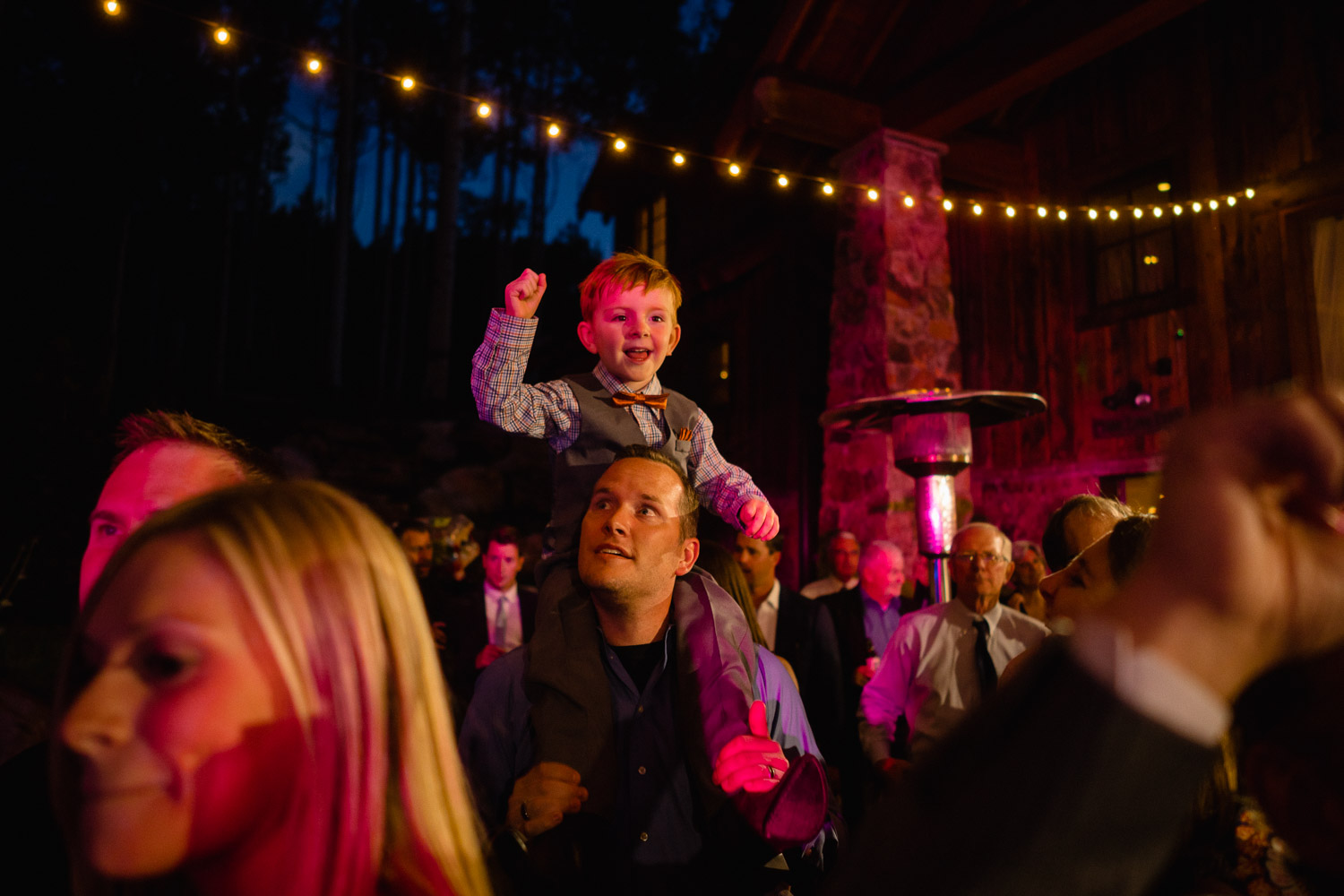 kid on man's shoulders with outside lights wedding