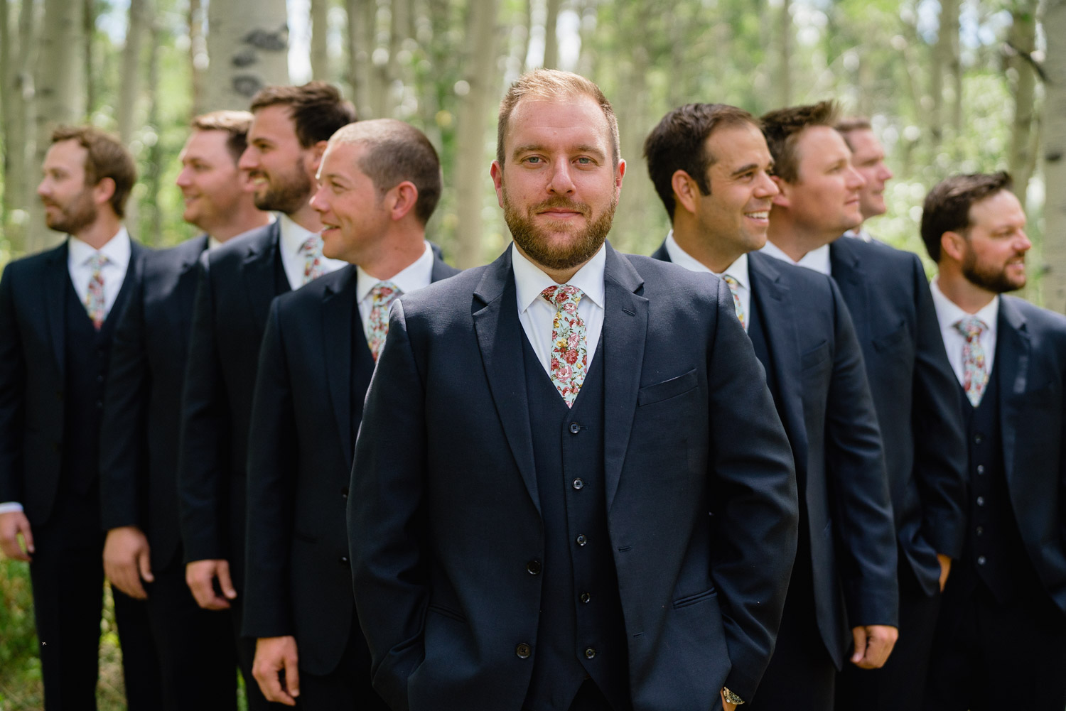 groom and best men wedding party outside with trees