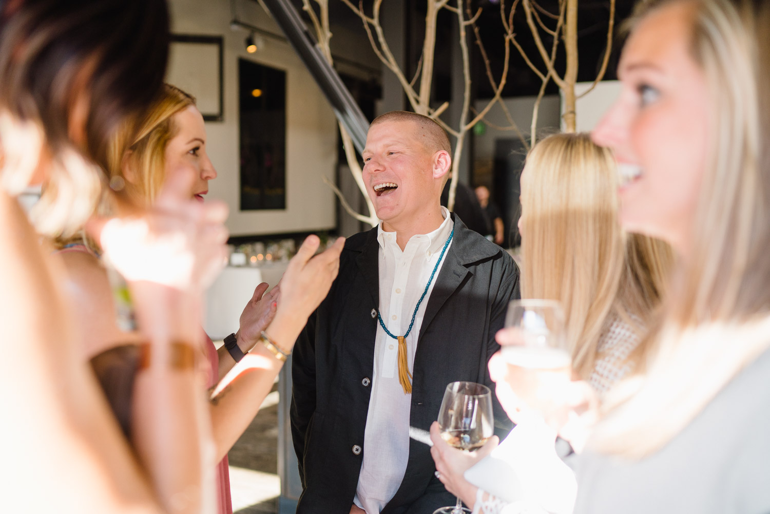 groom laughing interacting with rehearsal dinner guests riverhorse on main