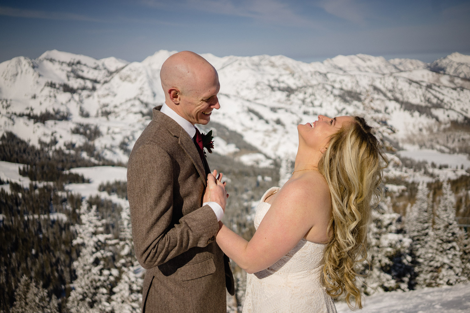 groom making bride laugh on snowy mountain