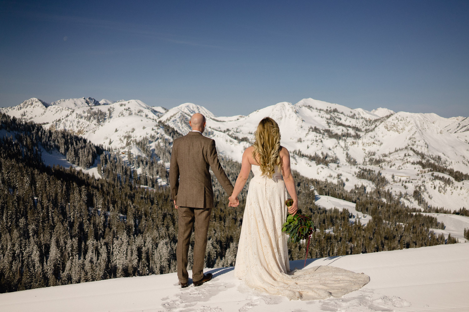 bride and groom hold hands on snowy mountain