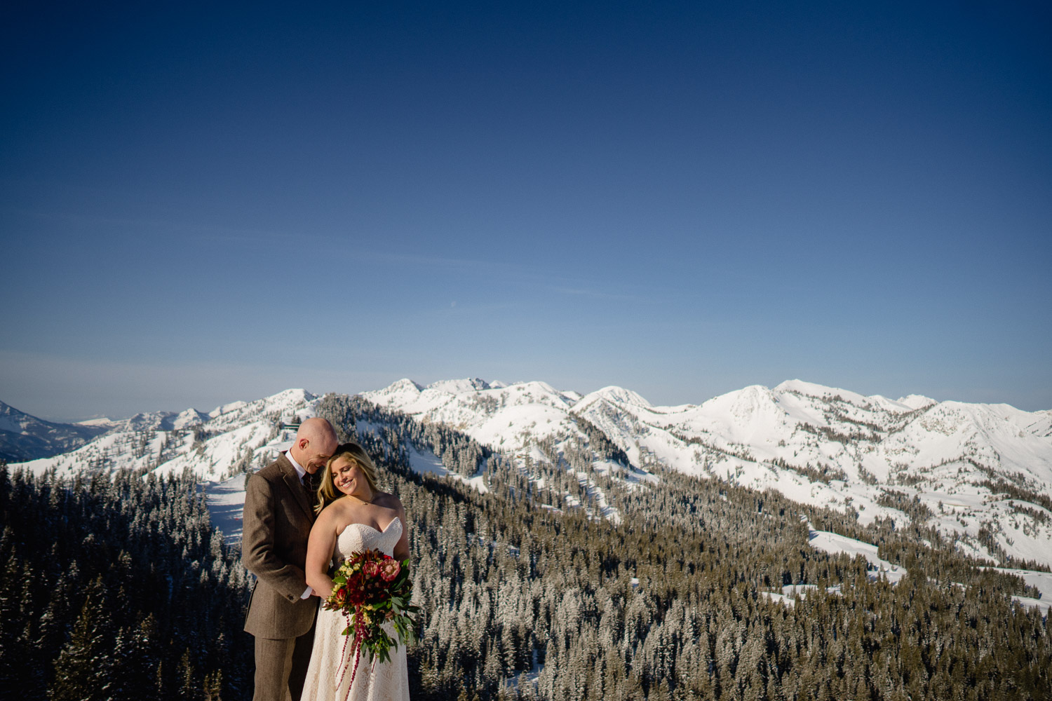 bride and groom embrace on mountain with trees