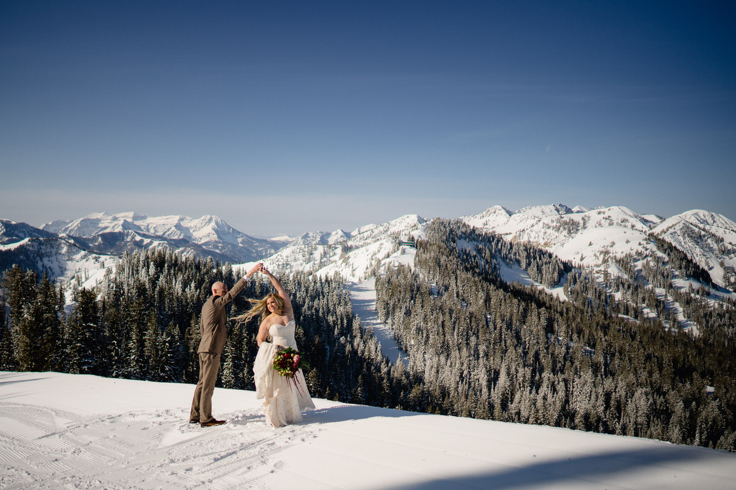 bride and groom dancing on snowy mountain with trees
