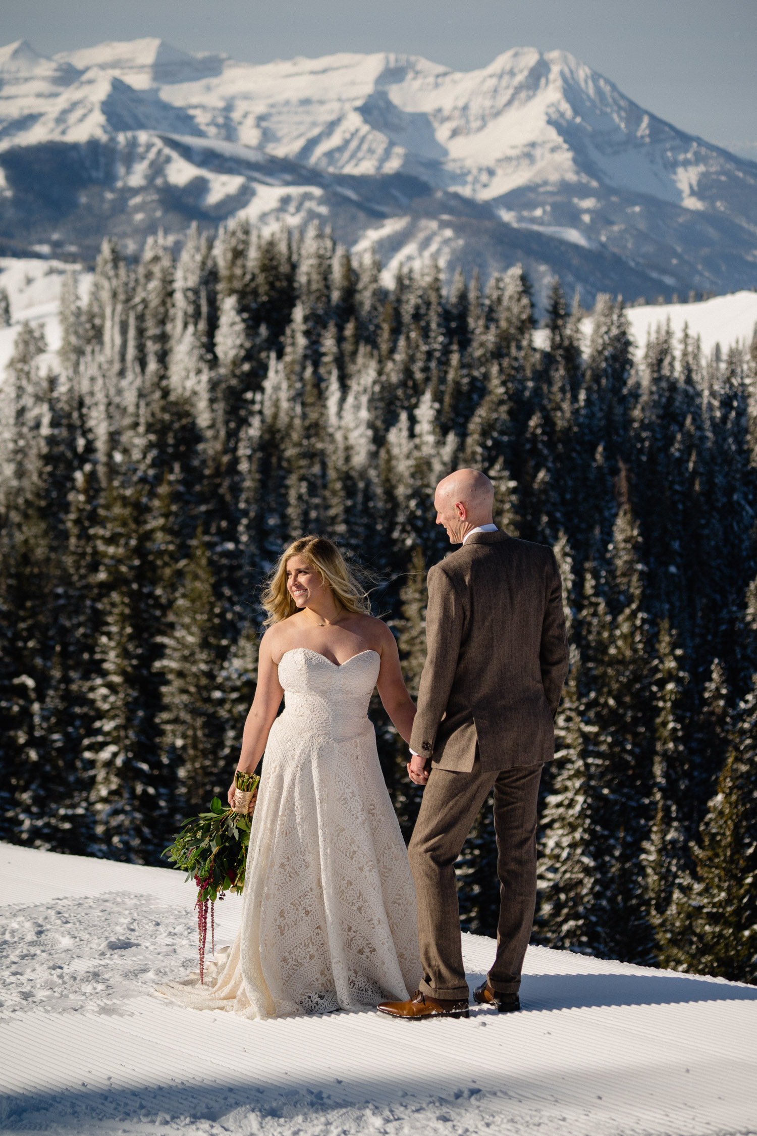 bride and groom on snowy mountain with trees