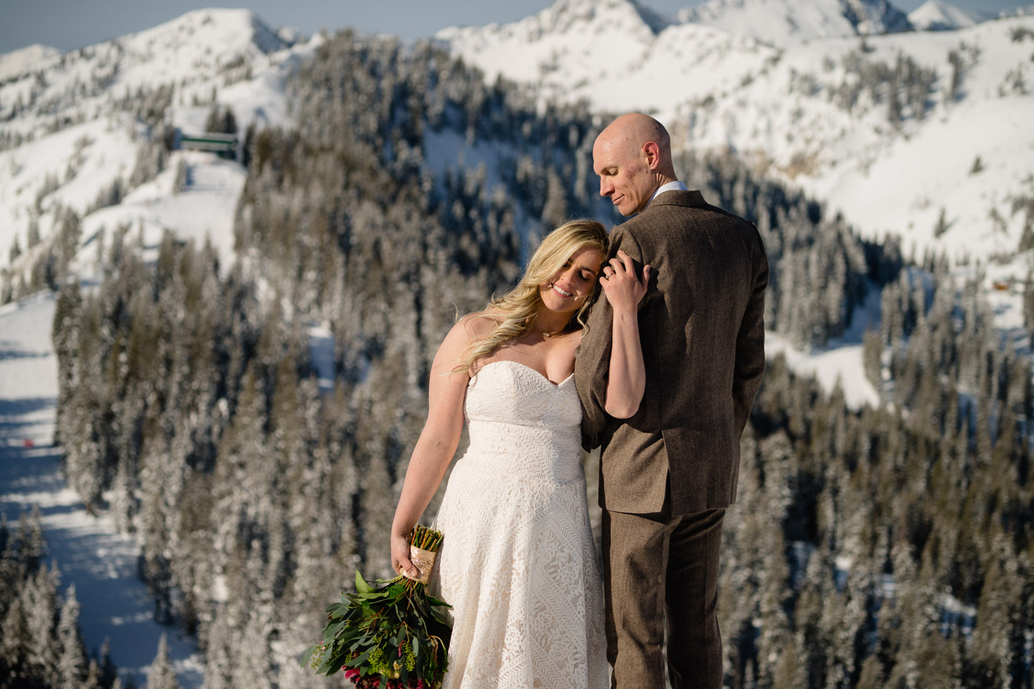 bride cuddles on groom on mountain top with trees