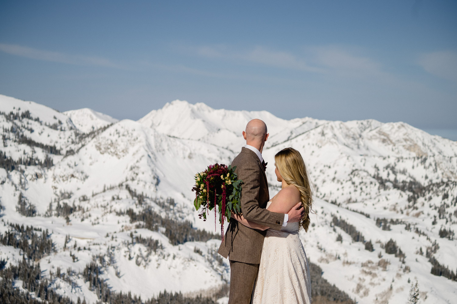 bride and groom looking at snowy mountain range