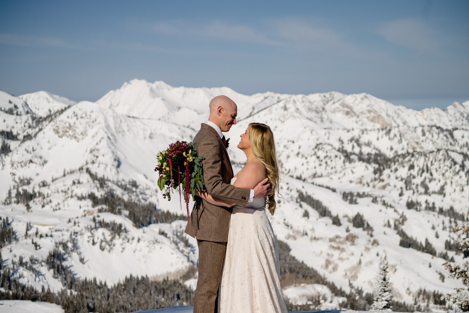 groom smiling at bride on snowy mountain at brighton resort