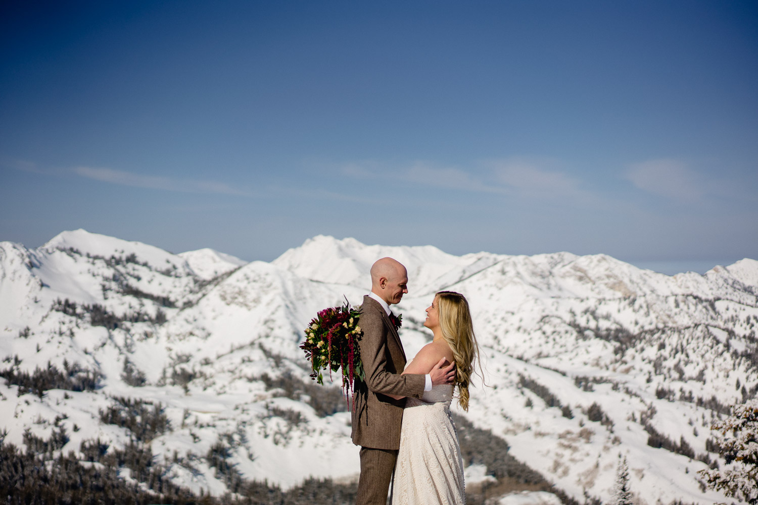 bride and groom gaze at each other embracing on mountain top