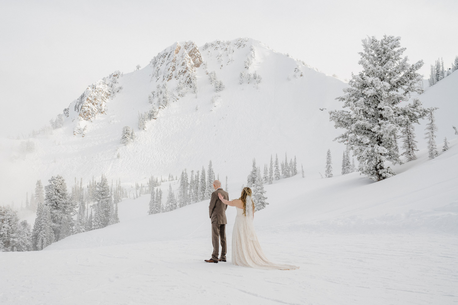 bride and groom on snowy mountain at snowbasin resort
