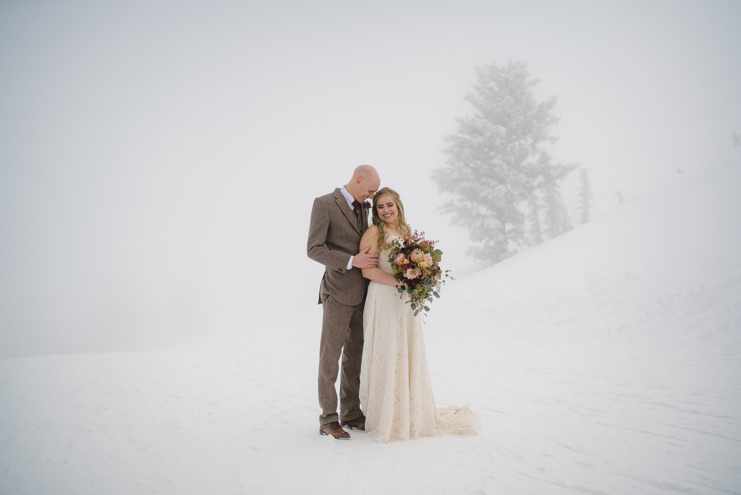 smiling bride and groom on snowy mountain snowbasin resort
