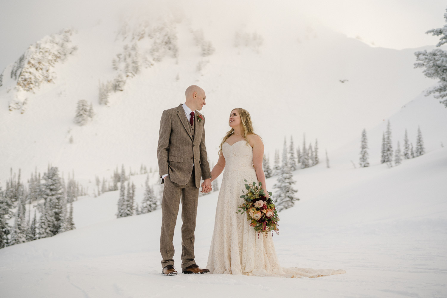 bride and groom on snowy mountain top snowbasin resort