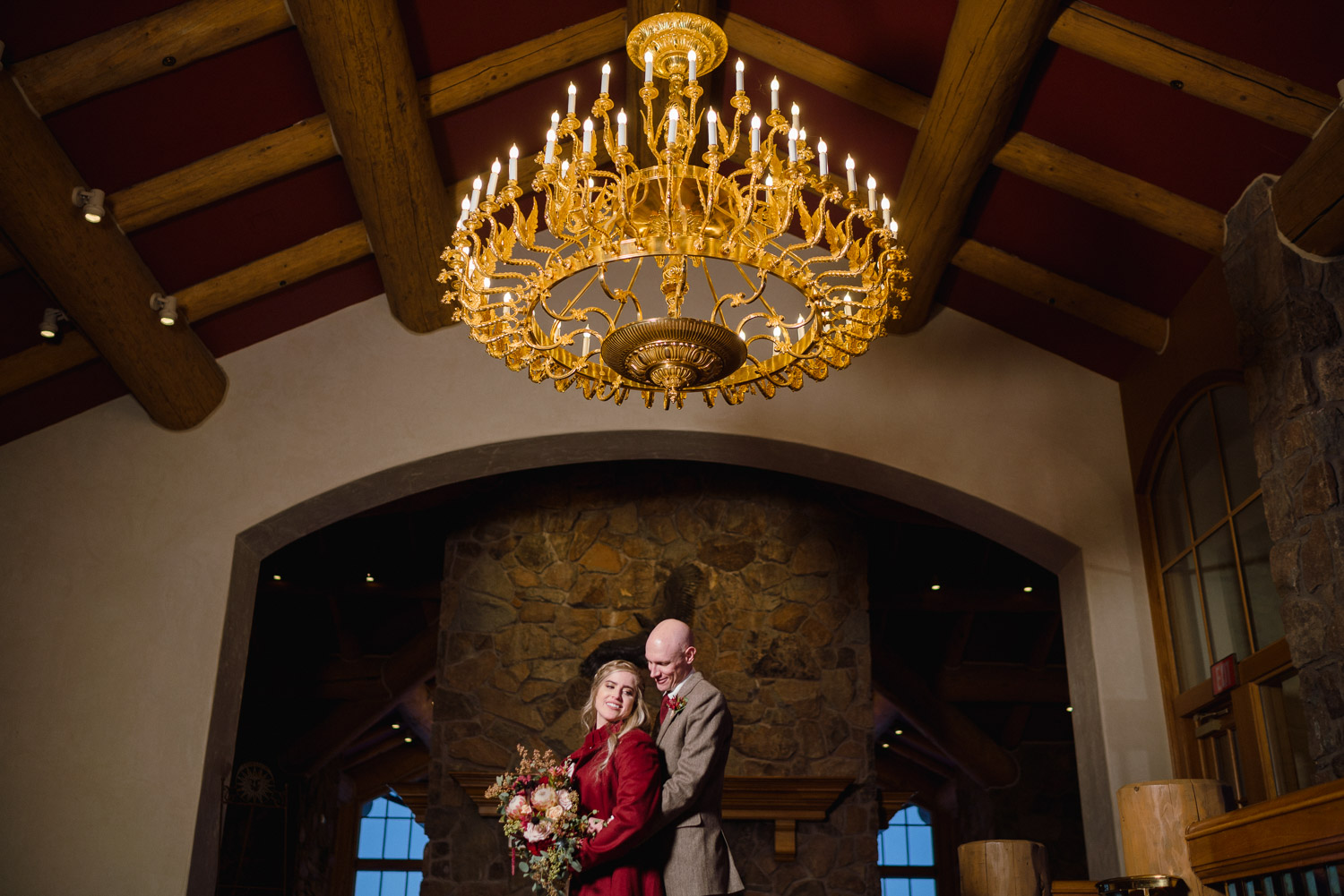 bride and groom under chandelier in lodge at snowbasin resort