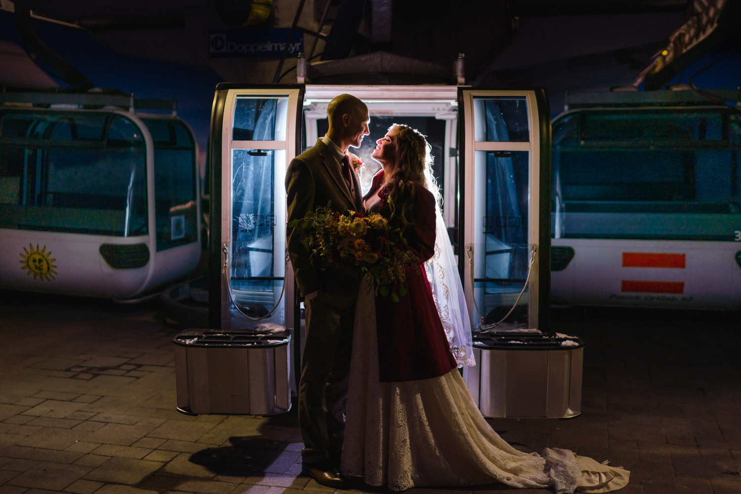 bride and groom in front of snowbasin resort tram at night
