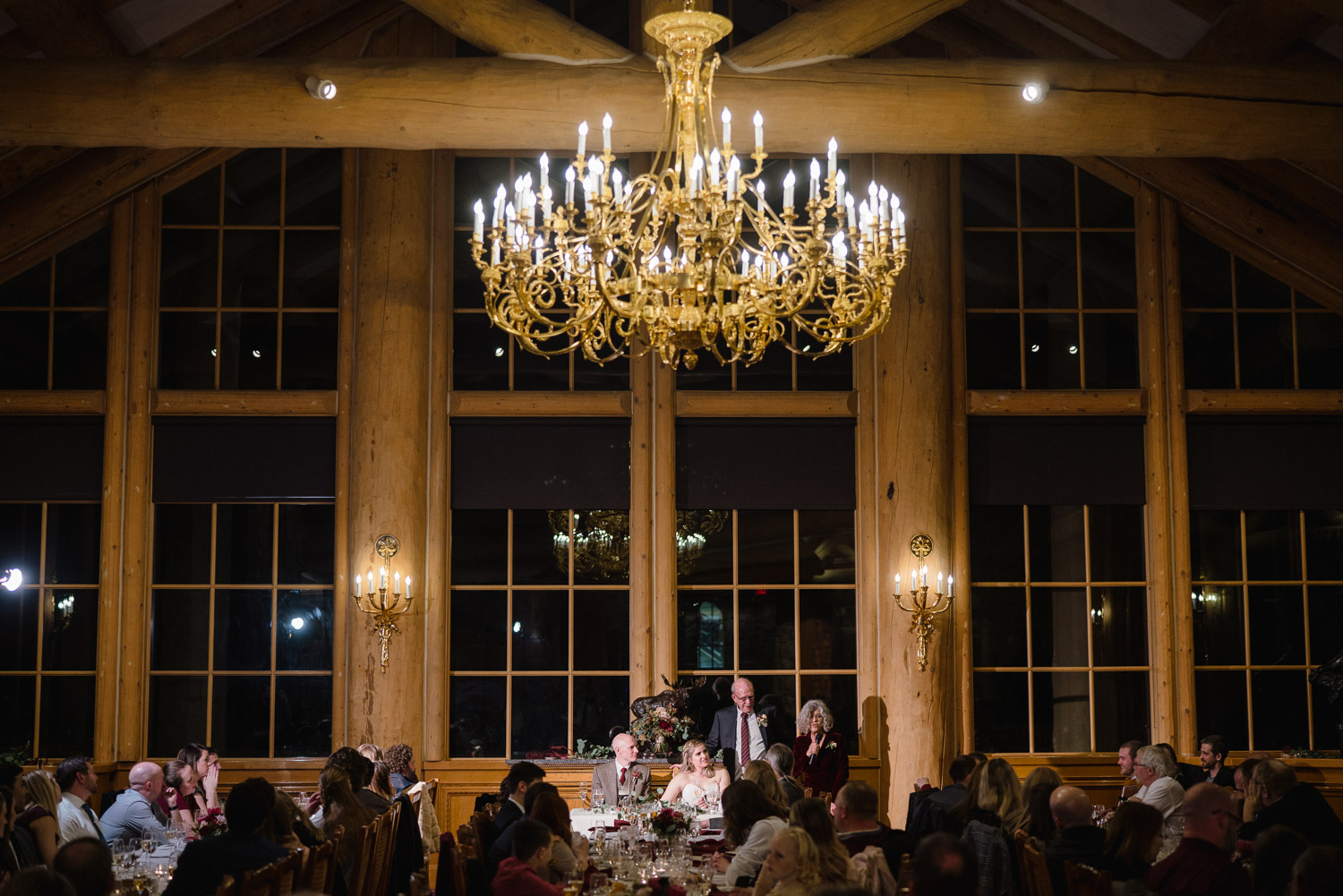 snowbasin wedding dinner and toasts under chandelier in lodge