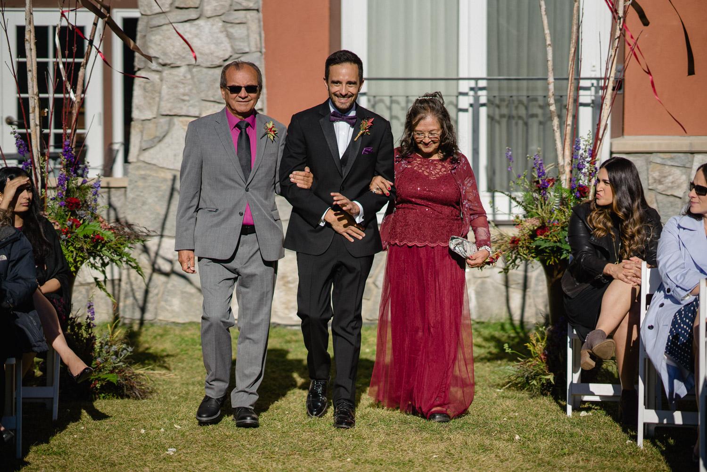 mom and dad walking groom down aisle utah fall wedding solitude resort