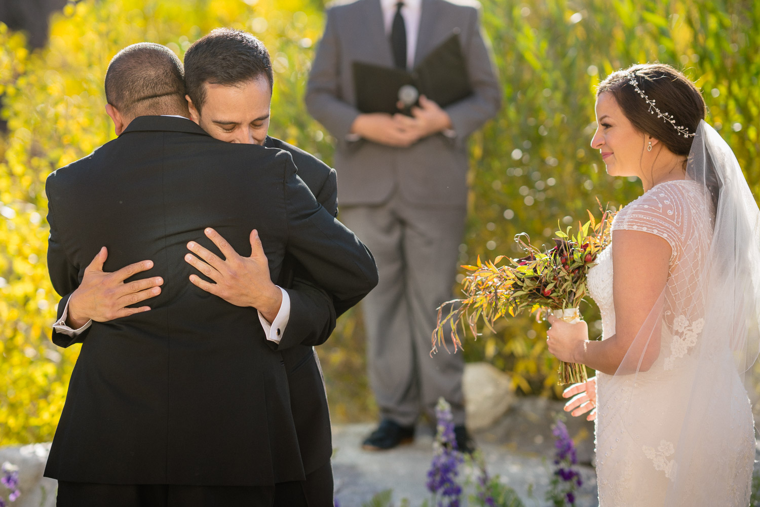 father of bride hugging groom bride observing utah fall wedding solitude