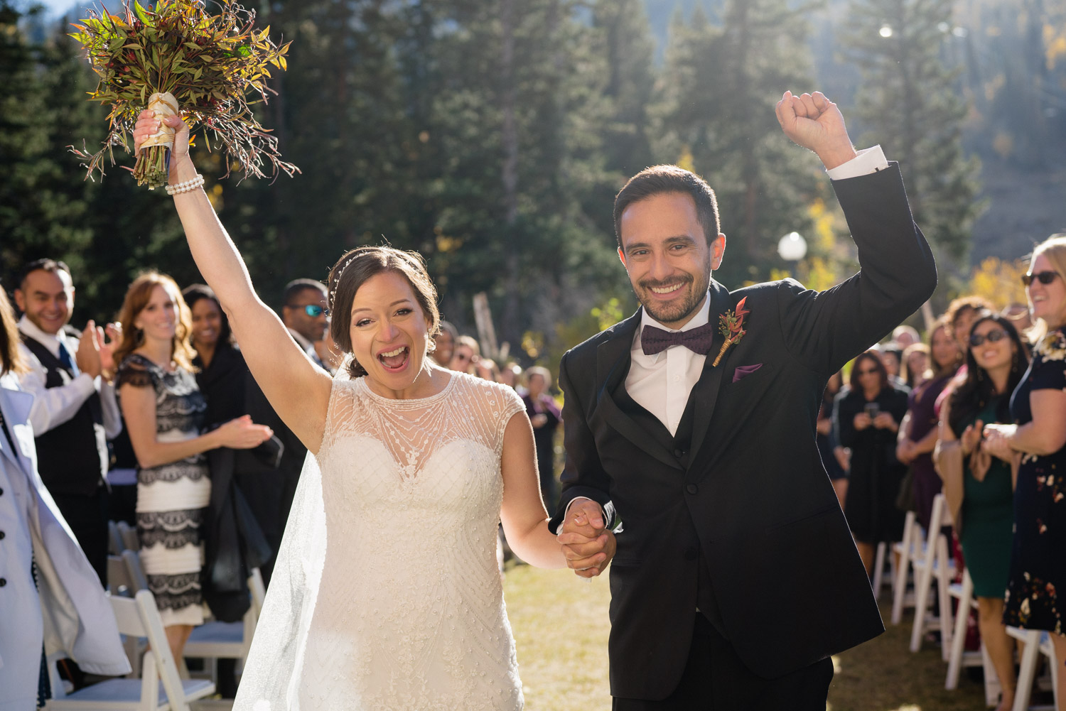 bride and groom walking down aisle celebrating with arms up outdoor fall wedding