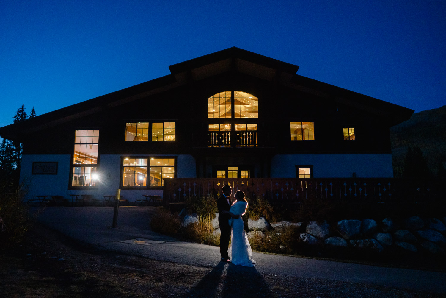happy couple standing outside at night in front of solitude lodge