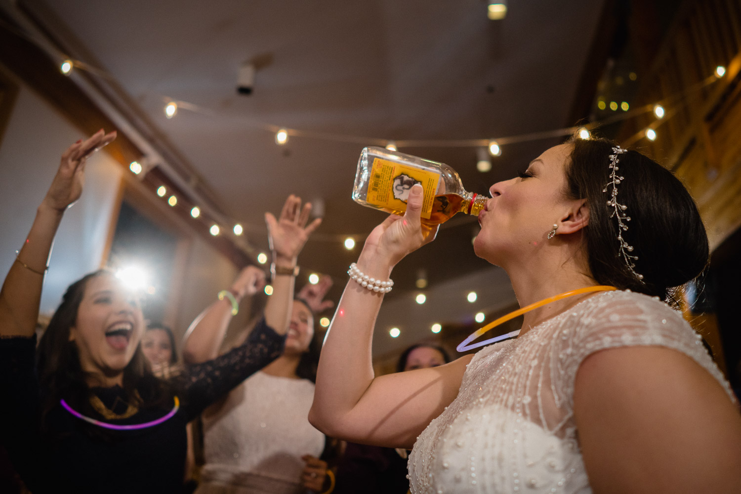 bride taking shot at wedding reception with guests cheering solitude resort utah